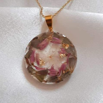 Collier avec pendentif rond en résine et fleurs séchées's image